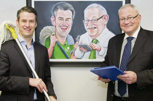 Just like the real thing – Outsource directors Graham Hughes and John Bannon beside a caricature by Niall O'Loughlin at the opening of their new offices in Drogheda.