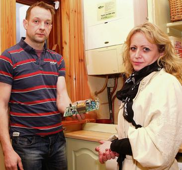 Emmanuel and Lisa McArdle, whose home was hit by a power surge, with their damaged boiler.