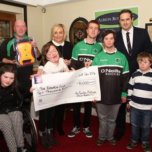 Liam Callan from Albion Rovers and Paddy Comyn, Volkswagen (sponsors) present cheque and defibrillator to Laura Doherty, Lauren Faulkner, Hannah Donnelly, Liam McDonnell, Jason McGivern and Ben McCann from The Rainbow Club