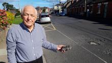 Eamonn McCarthy with the rock that broke off the road on Patrick Street