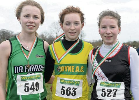 Eva Cummins, Boyne A.C. (centre) after taking silver in the U-15 Girls 2500m race in the Woodie's DIY Intermediate, Masters and Juvenile Development Cross-Country Championships of Ireland in Cow Park, Dunboyne, on Sunday last. Picture: Ramsey Cardy/Sportsfile