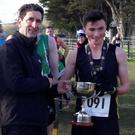 Andrew Duffin presents the Louis Duffin Cup to the first Dunleer AC man home in the senior race, Jack Boylan
