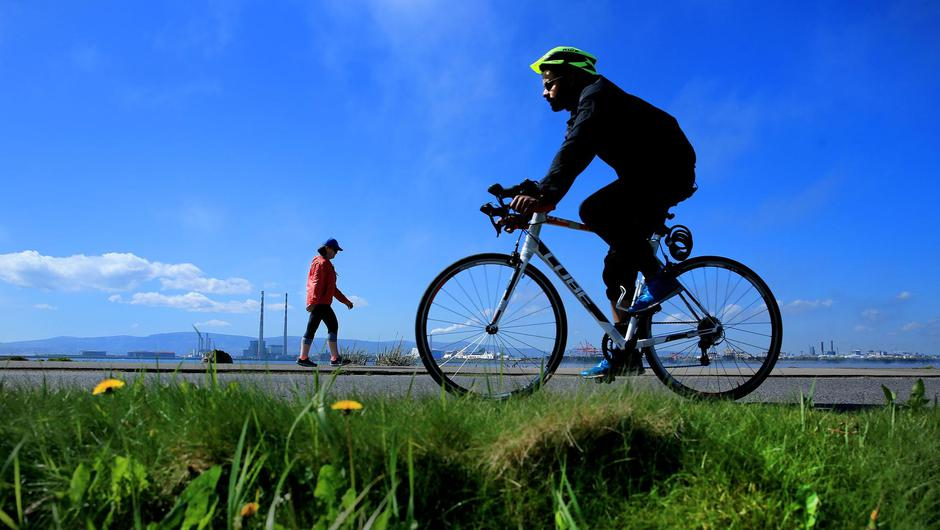 A walker and cyclist enjoy the fine weather on the Bull Wall in Clontarf. Pic: Gerry Mooney