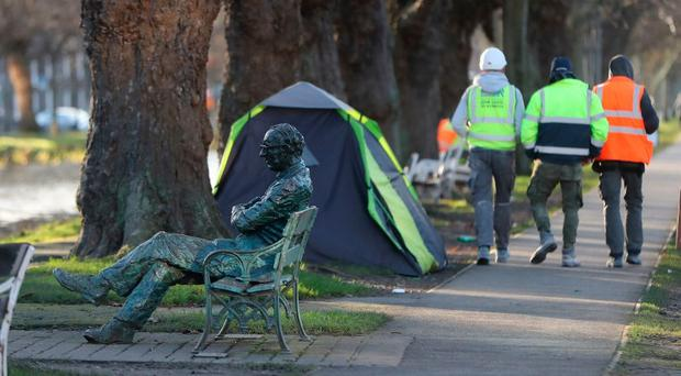 Builders walk by the tent of a homeless person in Dublin.