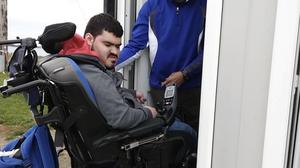 Jack Tanner demonstrating the difficulty in getting his wheelchair into the temproary toilet facilities at Brook Beach in Portrane.