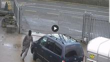 One of the masked raiders makes a hasty retreat back to the car after opening the gate.