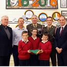 Fr Michael Byrne, principal Gerry Moran, Cmdt Eric Larkin, Lt Shane Flood and Minister Paul Kehoe with pupils Keith Roche, Tara Ennis and Cillian Dempsey during the presentation of the flag