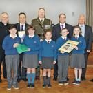 At St Aidan's Primary School. Front: Matt Kinnaird, Orla Kinsella, Orla Kinnaird and Seán and Eliza Conroy. Back: Lt Shane Flood, Fr Odhran Furlong, district manager Padraig O'Gorman, Lt Col Stephen Ryan, Minister Paul Kehoe. school principal Peter Creedon and Cpl Francis Farnan