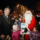 Enniscorthy Municipal District Chairman Cllr Paddy Kavanagh gives Santa Claus a hand as the Christmas lights are switched on in Enniscorthy on Saturday evening