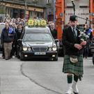 A piper leads the funeral cortege of David Walsh