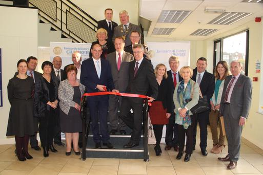 Paul Kehoe TD cuts the tape at the offices of Enniscorthy Chamber of Commerce, watched on by Wexford County Council CEO Tom Enright, Chamber president John Burke O'Leary, committee and invited guests