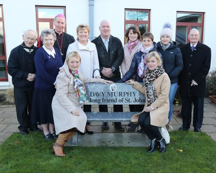 Family and friends of Davy Murphy with Bishop Denis Brennan at the unveiling of the bench at St John's Community Hospital.