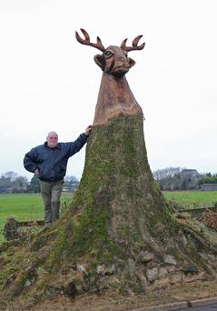 Leo Tector pictured with the sculpture by chainsaw artist John Hayes in Clonroche