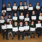 Pupils at St Senan's PS are presented with their certs for full attendance