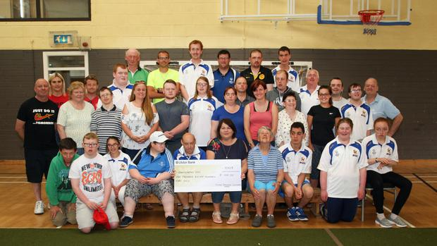 Fintan Broaders (centre) making a presentation to the Enniscorthy Special Olympics Club, proceeds from his sponsored walk