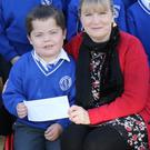 Principal Siobhan Doyle presenting a cheque to David Moran, on behalf of his sister Megan, with pupils and teachers