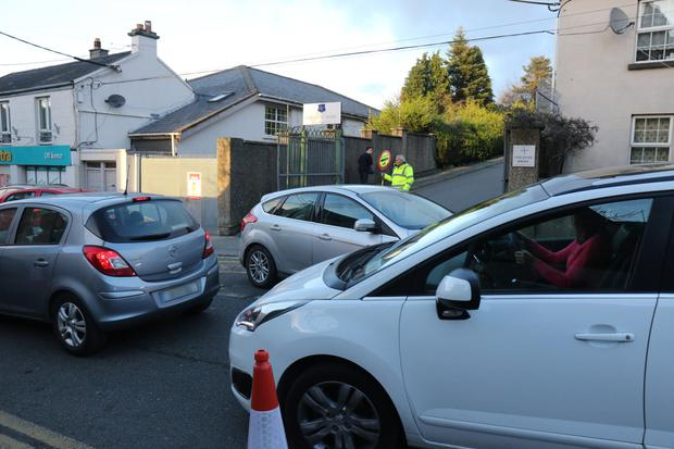 A lollipop man on duty at the entrance to Colaiste Bride