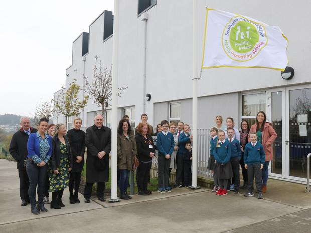 Eilish Ryan (6th. class) and Ivan (junior infants) raising of the new Healthy Ireland 'Health Promoting Schools' Flag in St Aidan's Parish School