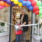 Jayden Warren cutting the ribbon with his mother Jacqueline at the official opening of Petite Cherie, Rafter St., Enniscorthy