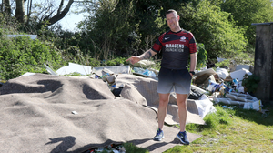 Billy Kinsella beside the mountain of rubbish covered with carpets at the back of his home