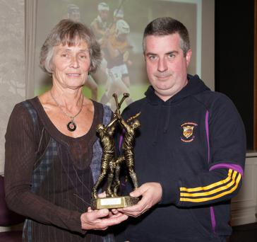 Marguerite Furlong making a presentation to the Faythe Harriers' Féile winning team at the recent Coiste na nÓg Convention. The award was accepted by Pat Henebery