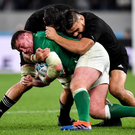 Tadhg Furlong is tackled by Samuel Whitelock and Angus Ta'avao of New Zealand