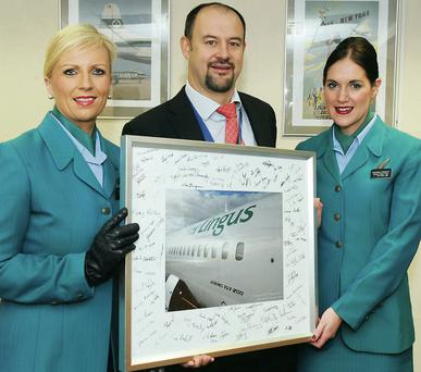 Colin Grant, Chief Executive of Air Contractors, presents a memento of the first trans-Atlantic flight of the company's Boeing 757 to Aer Lingus cabin crew members Leslie Murphy (left) and Grainne Frawley.