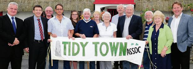 Members of Lusk Tidy Towns outside Anthony Rogan's Clay Cottage on the Dublin Road
