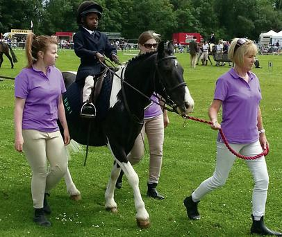 Six-year-old Taofeek Alimi from the RDAI Group in Broadmeadows taking part in the Trail Ride at the Dublin Horse Show