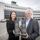 DAA Alcohol Retail Category Manager, Rachel Cartwright with Dublin Airport Managing Director, Vincent Harrison showcasing Dublin Airport's 75th Anniversary limited edition Powers Aviation Whiskey in front of the airport's original passenger terminal