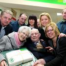 Long-serving Lusk Post office customer Joe Dennis (with wife Una) was the guest of honour at the opening of Lusk's new post office. He is seen here with Postmistress Linda Neary along with counter staff and local postpersons. Lusk post office has relocated to Supervalu on Station Road
