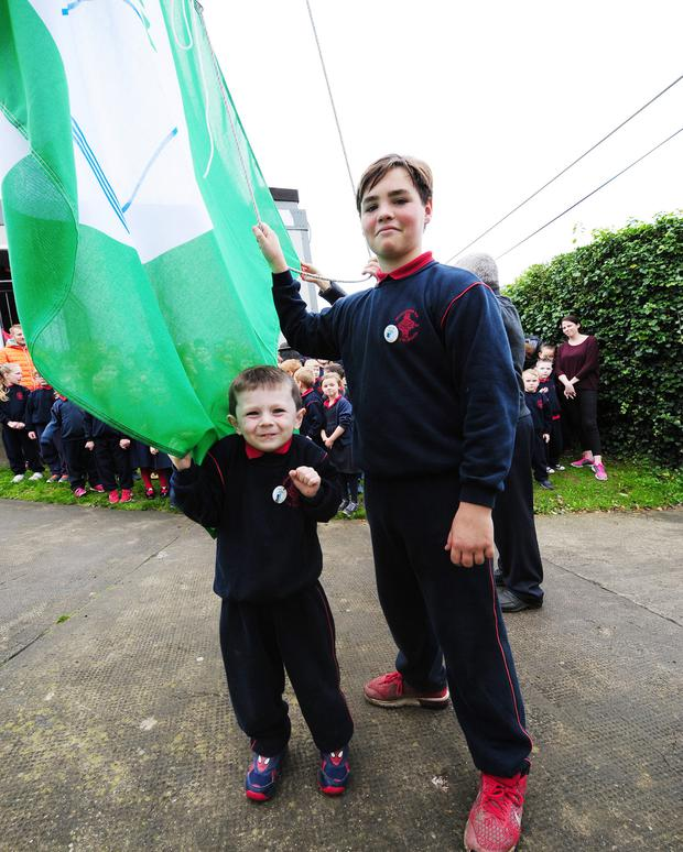 Youngest and oldest pupils raising the flag at Hedgestown NS green flag raising.
