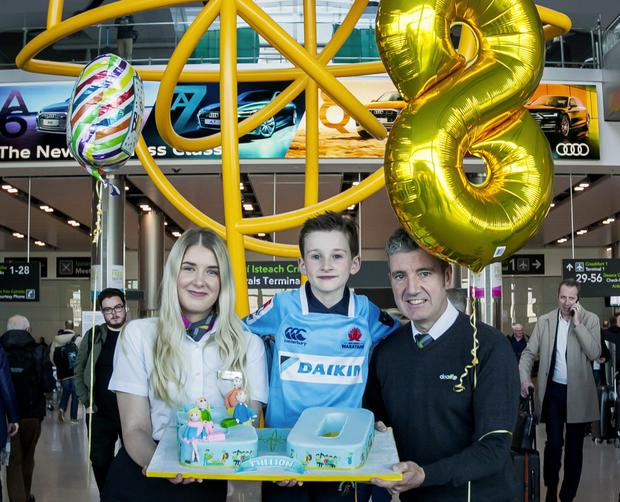 Celebrating Terminal 2's eighth birthday is Dublin Airport Retail Assistant, Simona Jurguliene; Aidan Meagher (age 8) visiting from Sydney and Michael Cooley, Dublin Airport Facilities