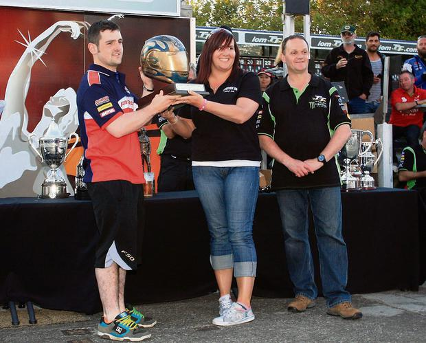 Michael Dunlop receives the Martin Finnegan Trophy from Marguerite Finnegan for the fastest Irish rider at the TT. Also pictured is 11-time TT winner Phillip McCallen. Picture: Jack Corry
