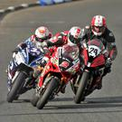Glen Irwin (2) and Alastair Seeley (34) both swoop past back marker Andrew Sellers (24), with Ian Hutchinson in the background, during their epic final Superbike lap at the North West 200. Photo: Jack Corry