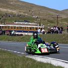 The TT is special as we see Debbie Barron powers past the Mountain Railway during a Sidecar race. Photo: Jack Corry