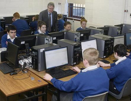 Deputy principal Eddie Crean with students in the computer room at Coláiste Abbáin.
