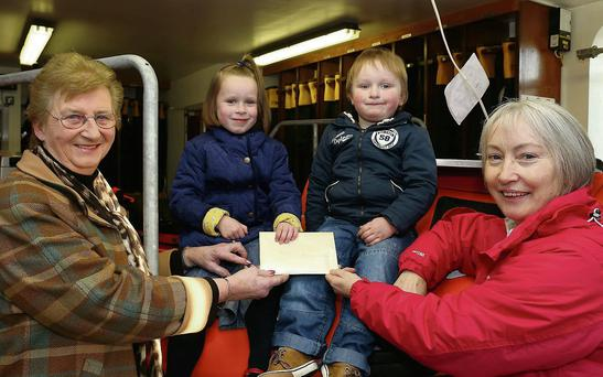 Arianna and Nathan, grandchildren of the late Neville Lazenby oversee the cheque presentation to the RNLI by Dorothea Lazenby, with the cheque being accepted by Mona Sheehan, treasurer of the fundraising committee.