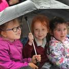 Amy Cloke, Molly Nolan and Leah Dunbar taking shelter at the official opening of the new classrooms at Kilmyshall NS