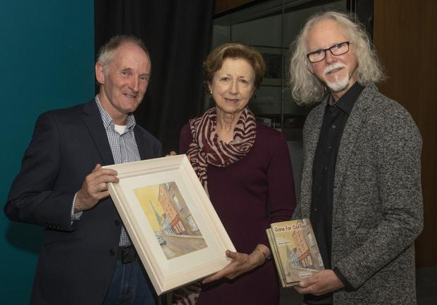 Producers of the Denis Collins poetry book, Kevin Lewis and Phillip Cullen, making a presentation to journalist and broadcaster Olivia O'Leary, who performed the launch