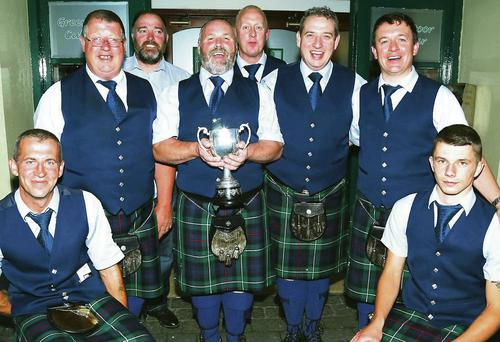 Pipe Major Tom Doyle holds the cup as band members celebrate their success in the Loch gCarman Arms.