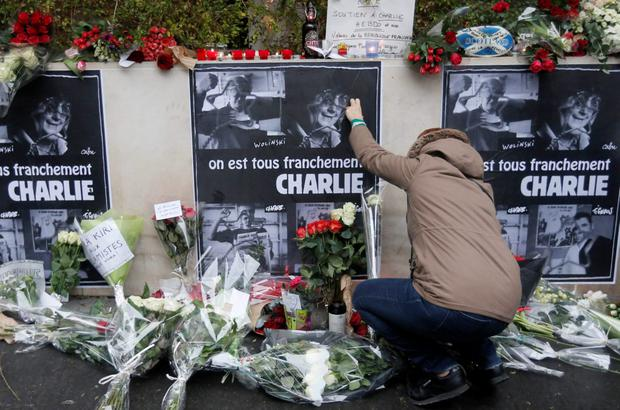 A person places flowers in front of the offices of weekly satirical newspaper Charlie Hebdo in Paris