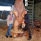 Sabine Rosler inspects Will Fogarty's work. He created a giant bear from a felled Redwood