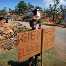 A Nepalese boy stands outside his village with a signboard asking for help in the aftermath of the devastating Nepal earthquake in 2015.
