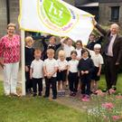 Siobhán Cullen of Heath Promoting Schools, HSE senior health promotion officer Nuala Harpur, school principal Matthew Meleady and teacher Yvonne Regan with the pupils and their new flag