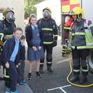 Pupils and firemen performing a mock rescue at the fire drill