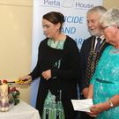 Orla Peare from Rosslare Harbour lights the candle, as Mayor of Wexford Jim Moore, and Sally Griffith look on