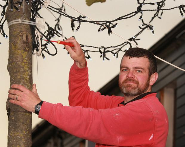 Electrician Keith O'Shea installing the lights on Gorey's Main Street.