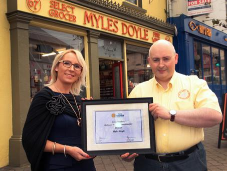 John Doyle of Myles Doyle select grocer and fine wine, Main Street, Gorey, receiving his presentation from Ashling Maher of Gorey Chamber of Commerce.