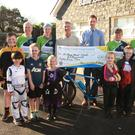 The Macamore Wheelers presented €1,800 to Ballygarrett NS following a sponsored cycle. Pictured are: Richard O'Connor, Sarah McKiernan, Sean Neary (treasurer), principal Niall Madden, Mary Cooper, and chairman Jimmy Crowe, watched on by school pupils.